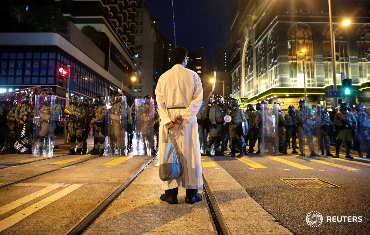 This priest, comes forward—seemingly out of nowhere—and confronts the police